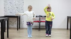 Two preschool girl dancing in domestic room Stock Footage
