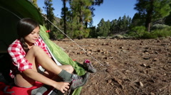 Camping woman tying hiking shoes walking from tent - stock footage