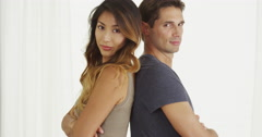 Mixed race couple standing back to back Stock Footage