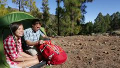 Camping couple in tent talking looking in backpack - campers in forest Stock Footage