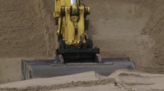 Close up excavator bucket digging in sand at construction site Stock Footage
