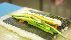 Adding cucumber to sushi roll Stock Footage