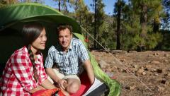 Camping couple in tent sitting looking at view - Campers smiling happy outdoors - stock footage