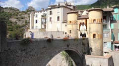 People walking in the entrance of the medieval city of Entrevaux, France Stock Footage