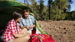 Camping couple in tent using smartphone - happy camper couple Stock Footage