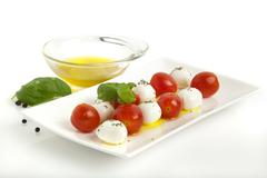 caprese salad with mini mozzarella balls and cocktail tomatoes - stock photo