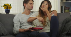 Interracial couple eating chips and guacamole on couch Stock Footage