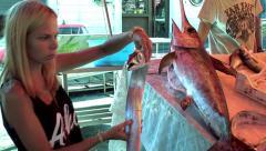 Girl examines silver scabbardfish at the Catania fish market. Sicily Stock Footage