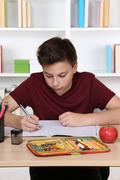 Young student writing in his exercise book at school Stock Photos