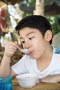 Little asian child enjoy eating an red ice cream Stock Photos