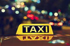 Taxi car on the street at night Stock Photos
