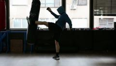 Boxing bag kicking, workout. Male model with hood Stock Footage