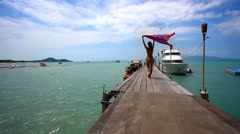 Beautiful young woman in bikini goes on bridge with pareo at windy day Stock Footage