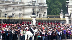 Buckingham Palace crowds and guards inside the gates Stock Footage