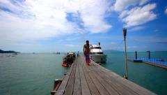 Beautiful young woman in bikini goes on bridge with pareo at windy day. Koh Stock Footage