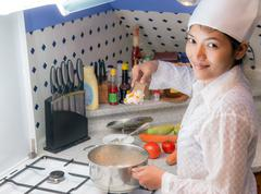 asian woman to cook in the kitchen - stock photo
