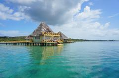 caribbean resort with thatched bungalow over water - stock photo