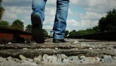 Man Walking Down Railroad Tracks Low Angle - stock footage