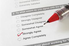 Closeup of a business survey, with strongly agree checked Stock Photos