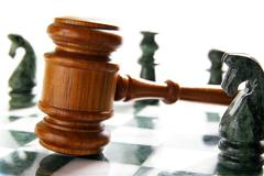 law gavel on a chess board with pieces - stock photo