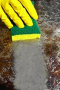 Sponge wiping a dirty metal surface clean Stock Photos