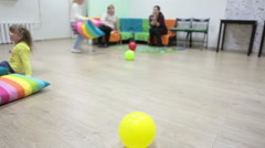 Domestic room with mothers talking and children playing. Focus on yellow balloon Stock Footage
