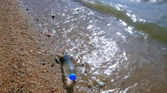 Waves of the sea beat on a water bottle in shore. HD. 1920x1080 Stock Footage
