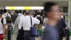 Zoom Out  / Time Lapse of  Commuters using Turn Style Tokyo Metrorail System Stock Footage