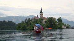 Man and woman in rowboat traveling to Bled church - stock footage