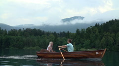 Rowboat on big pond with couple enjoying time - stock footage