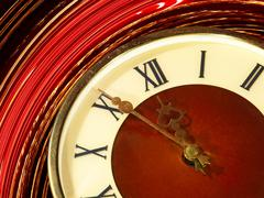 vintage clock face taken closeup on twirl abstract background. - stock photo