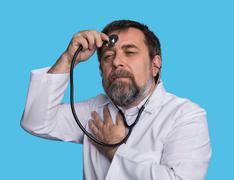 mad doctor with a stethoscope - stock photo