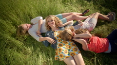 Playful Girls Laying In Grass, Have A Fun Tickle Fight - stock footage