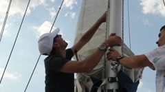 Closeup yacht crew letting down the sails. Yachting, sailing Stock Footage