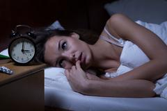 woman lying in bed sleepless - stock photo