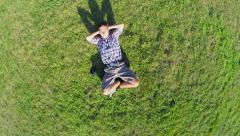 Happy man lying on grass hands behind head, aerial shot Stock Footage