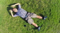 Young smiling male lies on grass, aerial vertical shot, zoom-out Footage