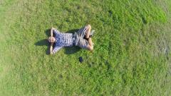 Aerial, young positive man lying on ground hands behind head Stock Footage