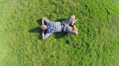 Aerial vertical shot of happy male lying on grass, zoom-out Stock Footage