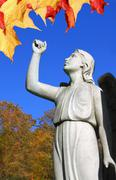 angel statue in cemetary with raised arm and leaves - stock photo