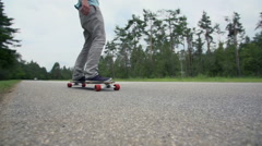 Longboard skater passing by the camera close up Stock Footage