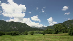 Driving by a nature landscape with green forest under blue sky with clouds - stock footage