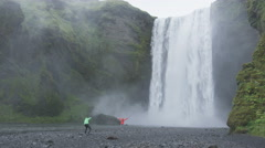 Waterfall Skogafoss on Iceland with tourists taking photo - SLOW MOTION Stock Footage