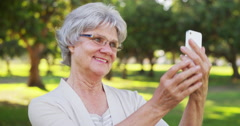Senior woman taking selfies at the park Stock Footage