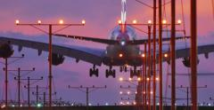 Jumbo jet airplane plane landing in airport in Los Angeles at sunset. 4K UHD - stock footage
