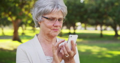 Senior woman texting on smartphone at the park Stock Footage