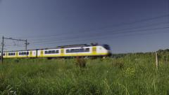 Dutch train passing by in beautiful countryside Stock Footage
