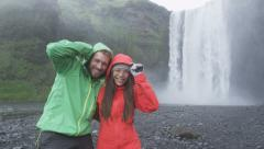 Iceland tourists couple by waterfall Skogafoss - RED EPIC SLOW MOTION Stock Footage