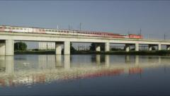 High speed train on viaduct with mirrored image in the water Stock Footage