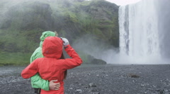 Iceland tourists people fun by waterfall Skogafoss - stock footage